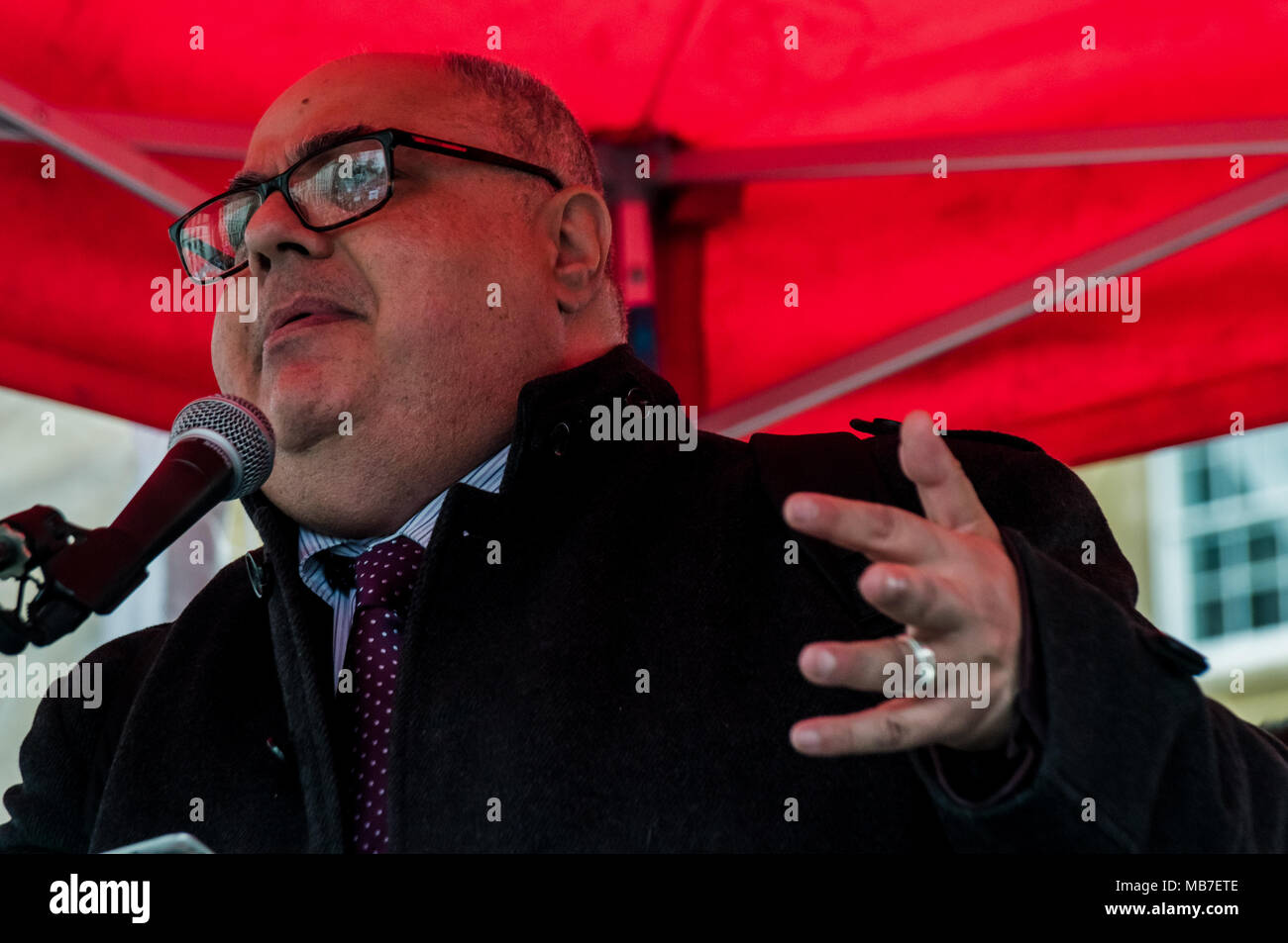 April 7, 2018 - London, UK. 7th April 2018. Kamel Hawwash, Palestine Solidarity Campaign, speaks at the protest at Downing St condemning the shooting by Israeli snipers of peaceful unarmed Palestinian protesters on the first day of a peaceful protest, the Great March of Return, at the separation wall in Gaza on Land Day, 30th March. Live fire by the Israelis killed 17 and wounded over 750. A further nine Palestinians including one journalist were killed yesterday and 1,350 injured, around 400 by live fire, with around 25 in a critical condition. There were many speeches condemning the Israe - Stock Image