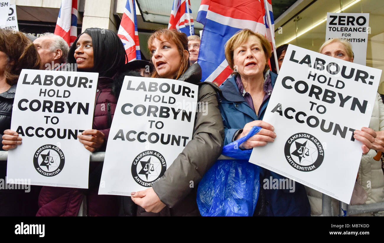 London, UK  8 April 2018. Demonstrators with signs at a protest calling for Jeremy Corbyn, leader of the Labour party, to be held called to account following reported anti-semitism within the party.  The event was organised by the Campaign Against Anti-Semitism, outside the Labour Party's headquarters in central London.   Credit: Stephen Chung / Alamy Live News - Stock Image
