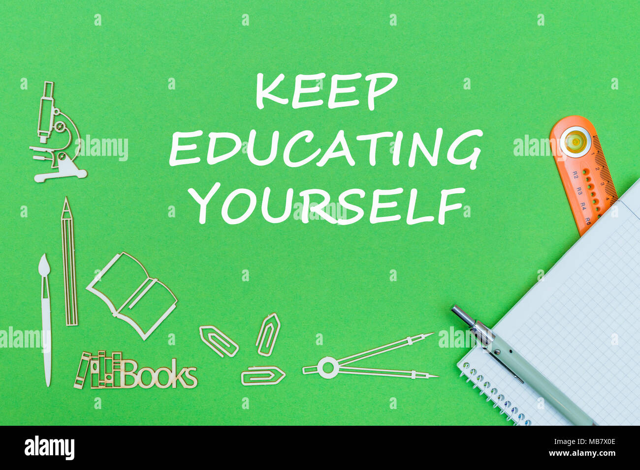 concept school, text keep educating yourself, school supplies wooden miniatures, notebook, ruler, pen on green backbord - Stock Image