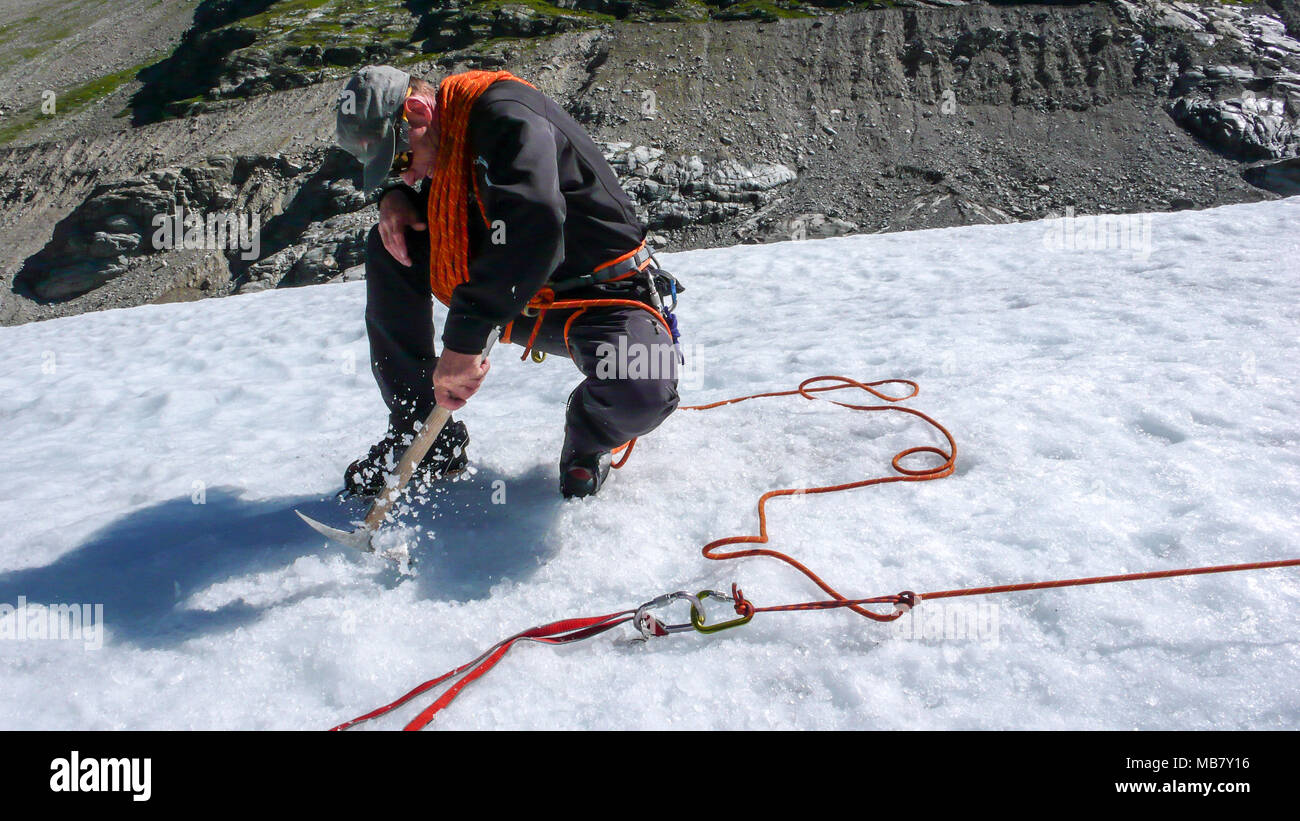 one male mountain guide installing a pulley system for crevasse rescue on a glacier - Stock Image