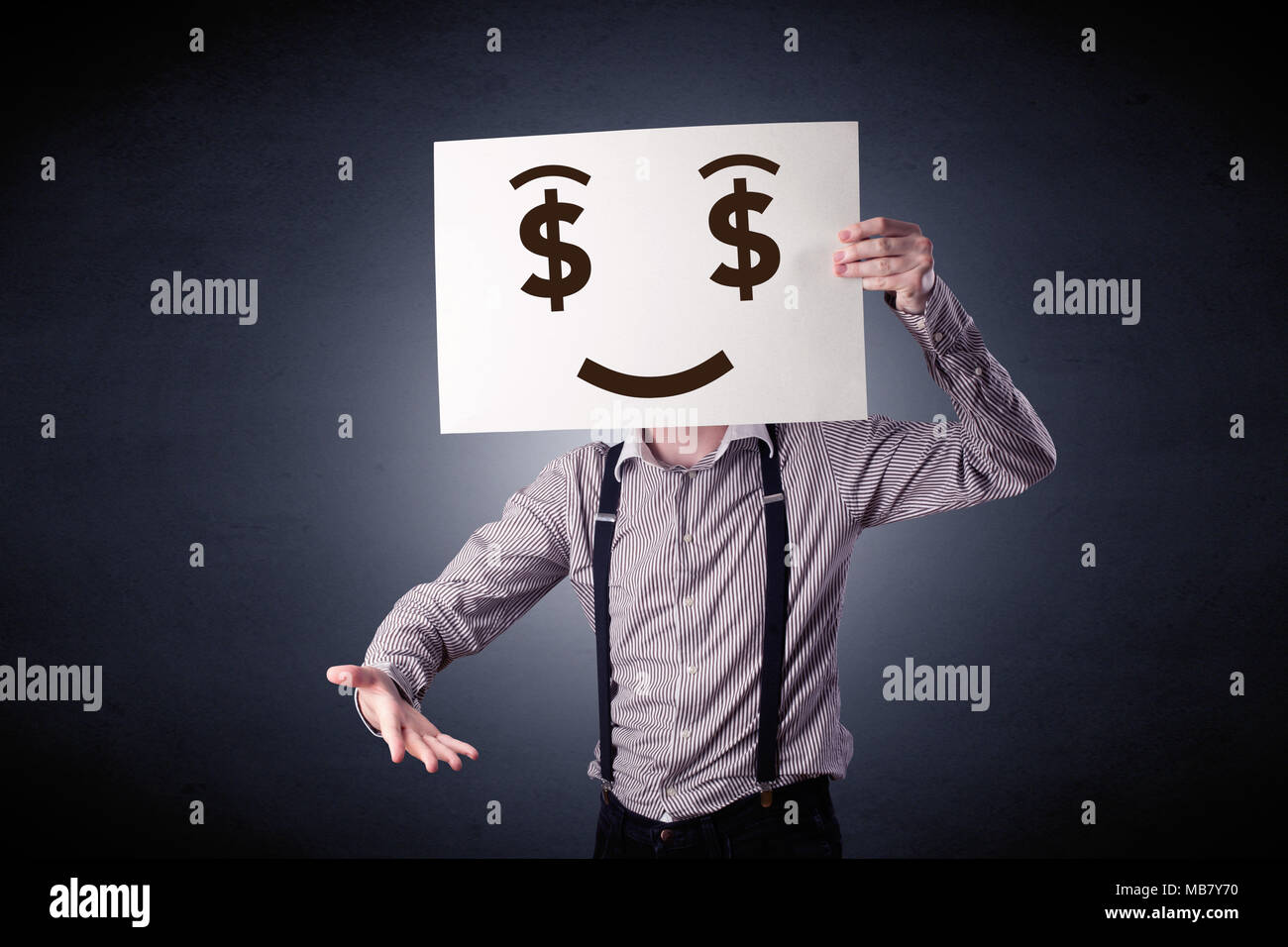 Young casual businessman hiding behind a greedy face drawing on cardboard - Stock Image