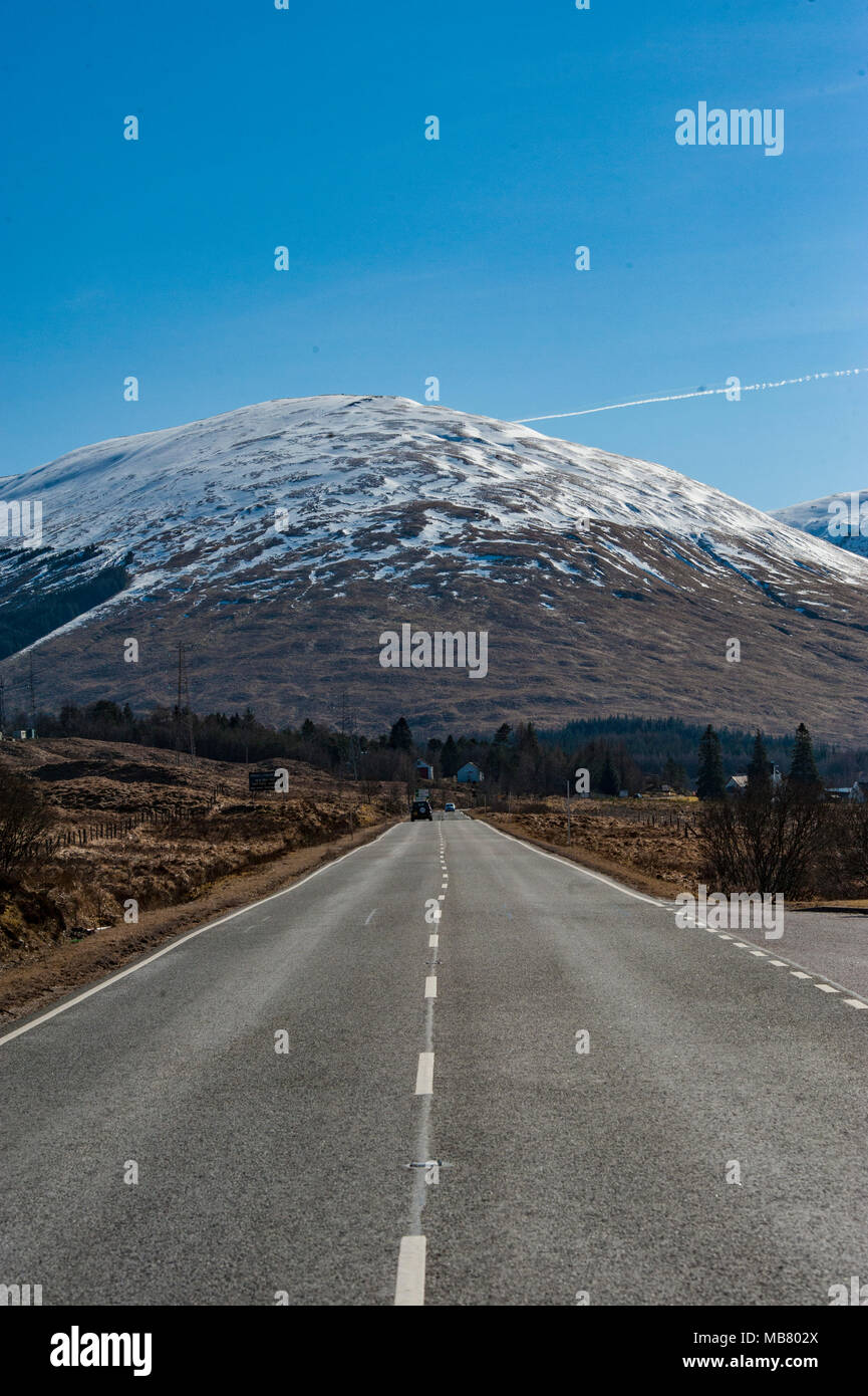 A deserted, empty road in the Scottish Highlands with snow capped mountains near the historic site of Glencoe, one of the great drives in Europe. Stock Photo