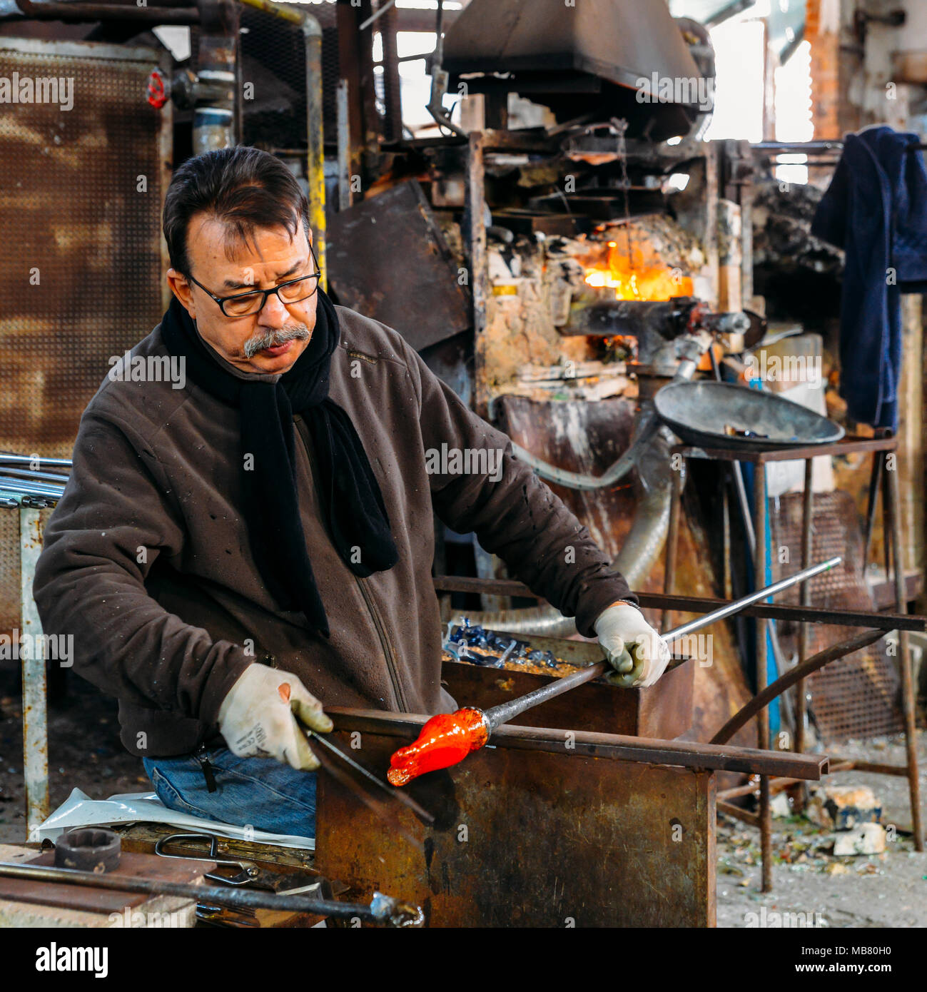 Traditional glass blower forming a beautiful piece of glass in a workshop - Stock Image