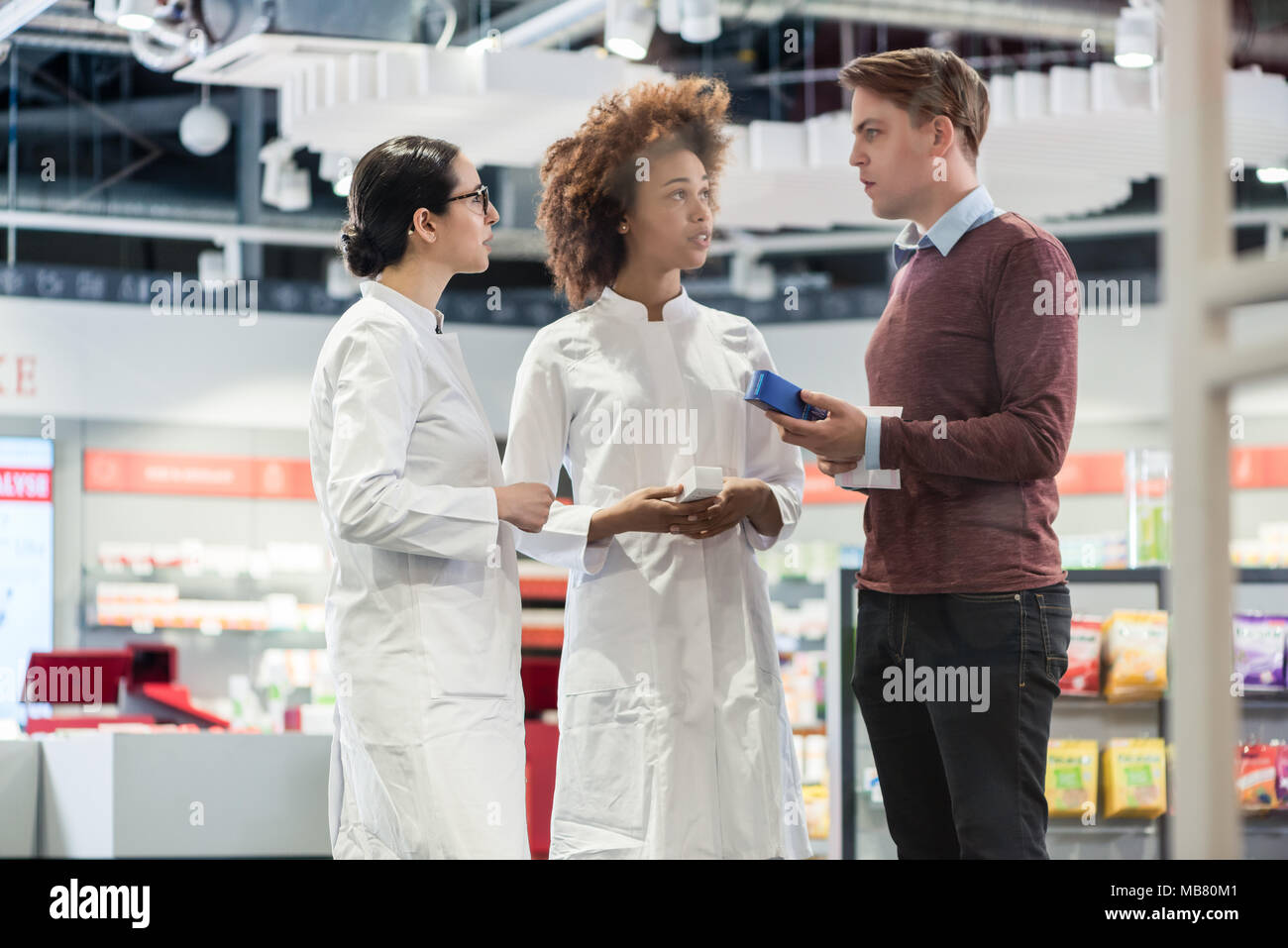 Young man asking for opinion from pharmacists regarding prescribtion - Stock Image