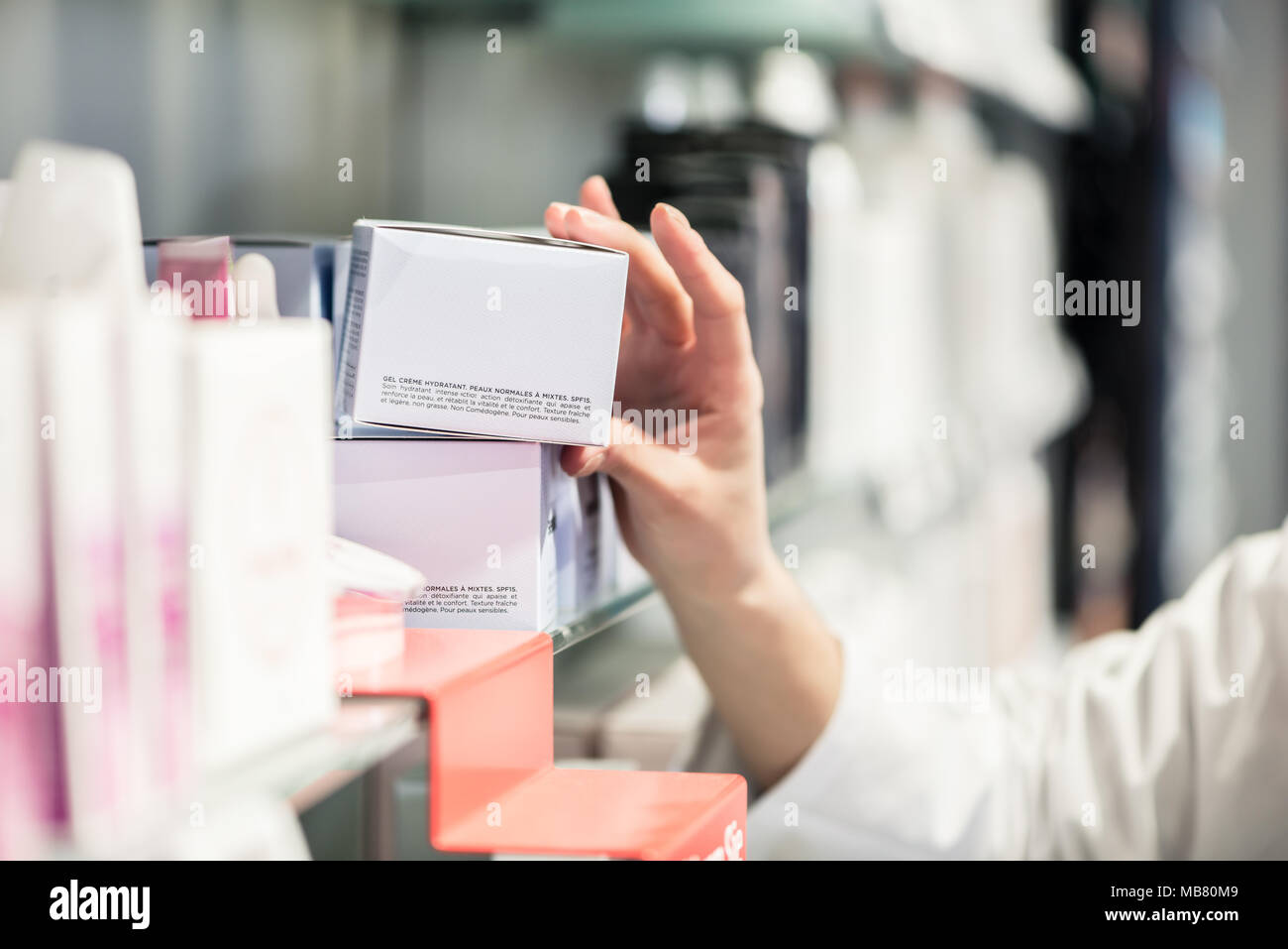 Close-up of the hand of female pharmacist picking up the best product - Stock Image