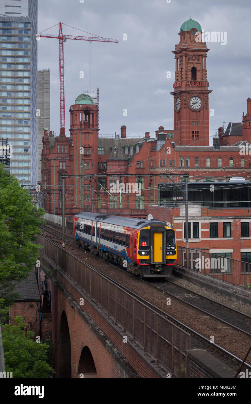 A East Midlands Trains class 158  train on the congested railway between Manchester Oxford Road an Piccadilly on Castlefield viaduct. - Stock Image