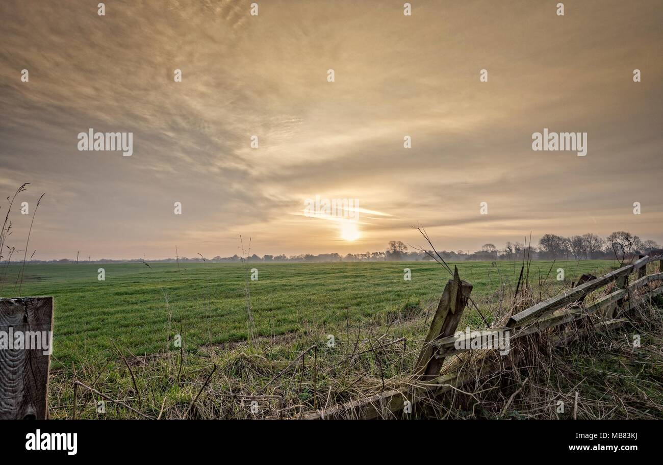 Dawn falls on a newly planted field.  The sun is prominent in the dramatic sky and a collapsed wooden fence is in the foreground. - Stock Image