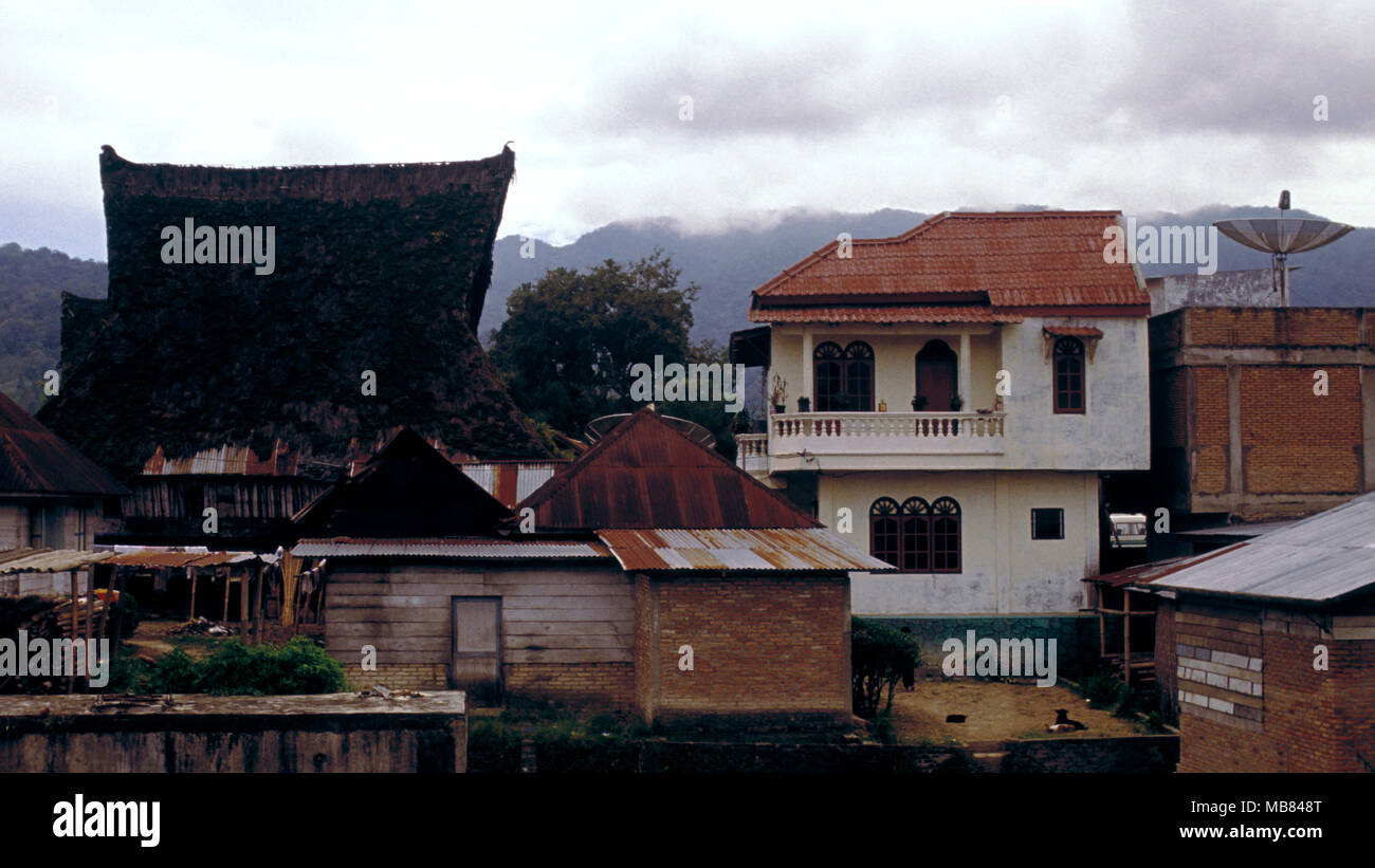 In Karo Batak villages, Sumatra, Indonesia, modern construction is replacing the traditional longhouses that were built hundreds of years ago. - Stock Image