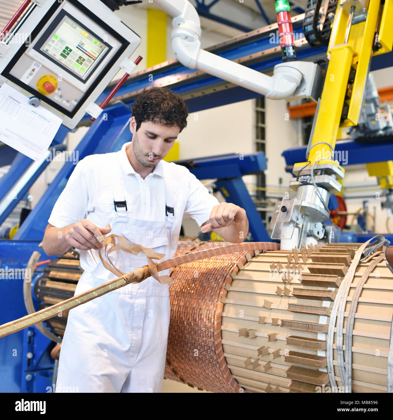young mechanical engineering workers operate a machine for winding copper wire - manufacture of transformers in a factory - Stock Image