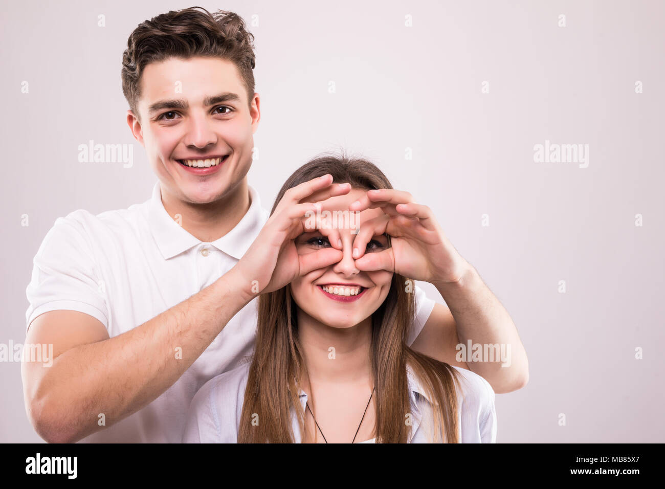 Concept of having funtime and grimacing, behaving like kids. Close up photo of two happy people making binoculars with their hands and showing tongues - Stock Image