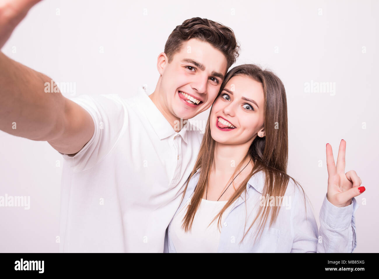 Handsome man making selfie with his pretty woman gesturing v-sign - Stock Image
