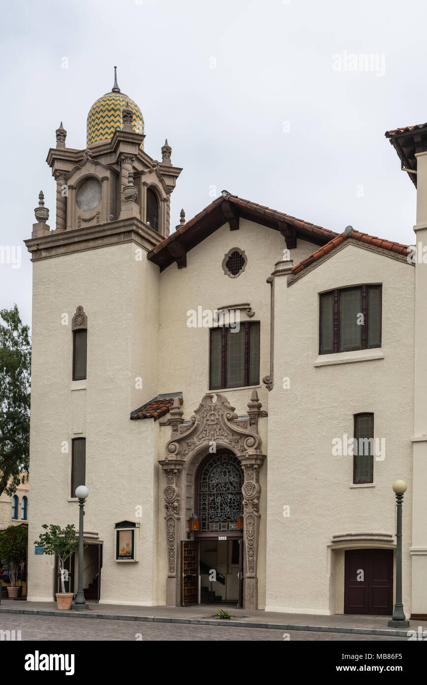 Los Angeles, CA, USA - April 5, 2018: Historic Plaza Methodist Church on El Pueblo Plaza corner of Olivera Street under silver sky. Yellow facade, bel - Stock Image