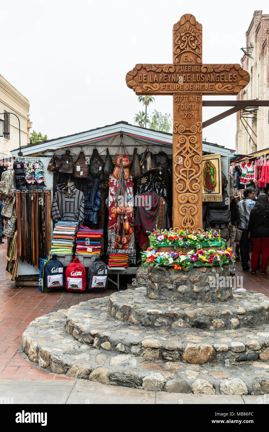 Los Angeles, CA, USA - April 5, 2018: At historic El Pueblo Plaza stands brown chiseled wooden cross as memorial of the founding of the town by Felipe - Stock Image