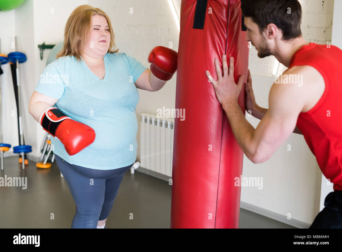 Obese Woman Boxing in Gym - Stock Image