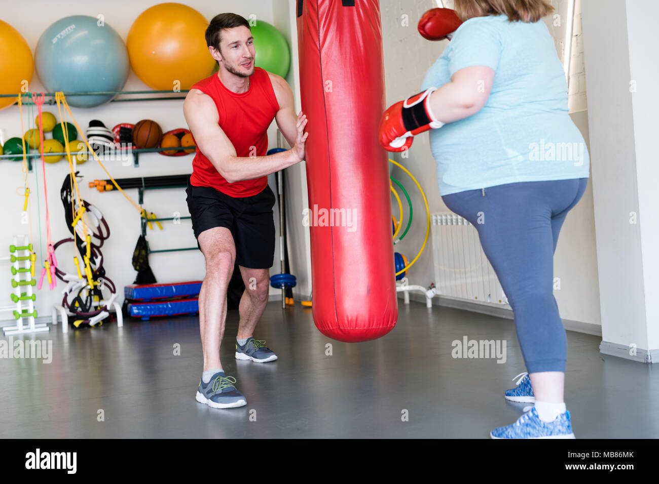 Fitness Trainer Helping Overweight Woman - Stock Image