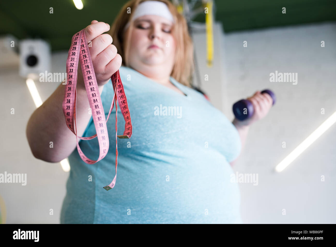 Anxious Obese Woman with Tape Measure - Stock Image