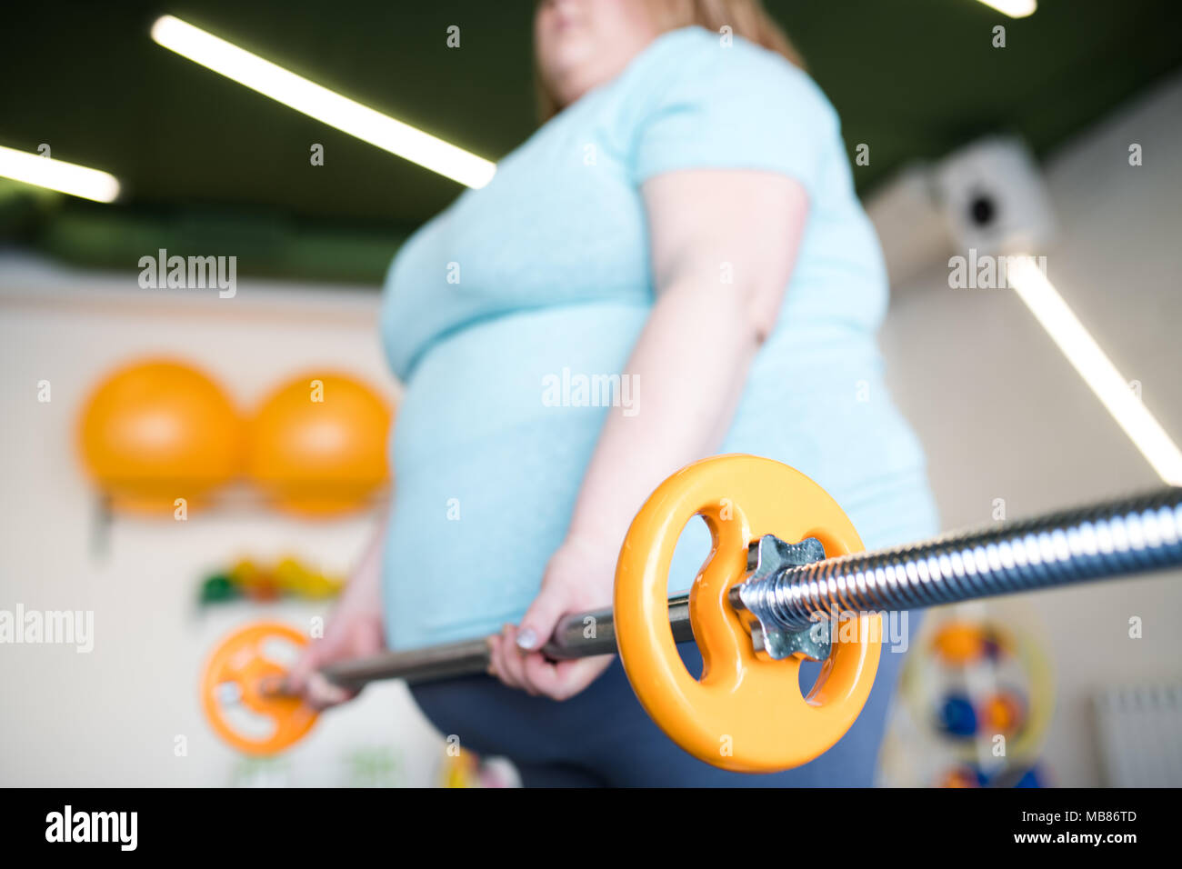 Overweight Woman Working Out with Barbell - Stock Image