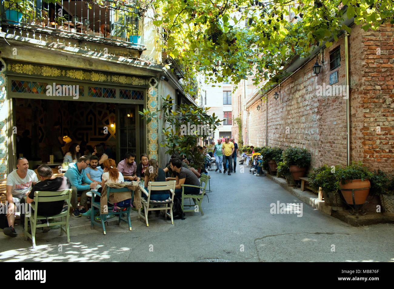 People enjoy nice weather at famous cafe in hip neighborhood Karakoy in Istanbul. Stock Photo