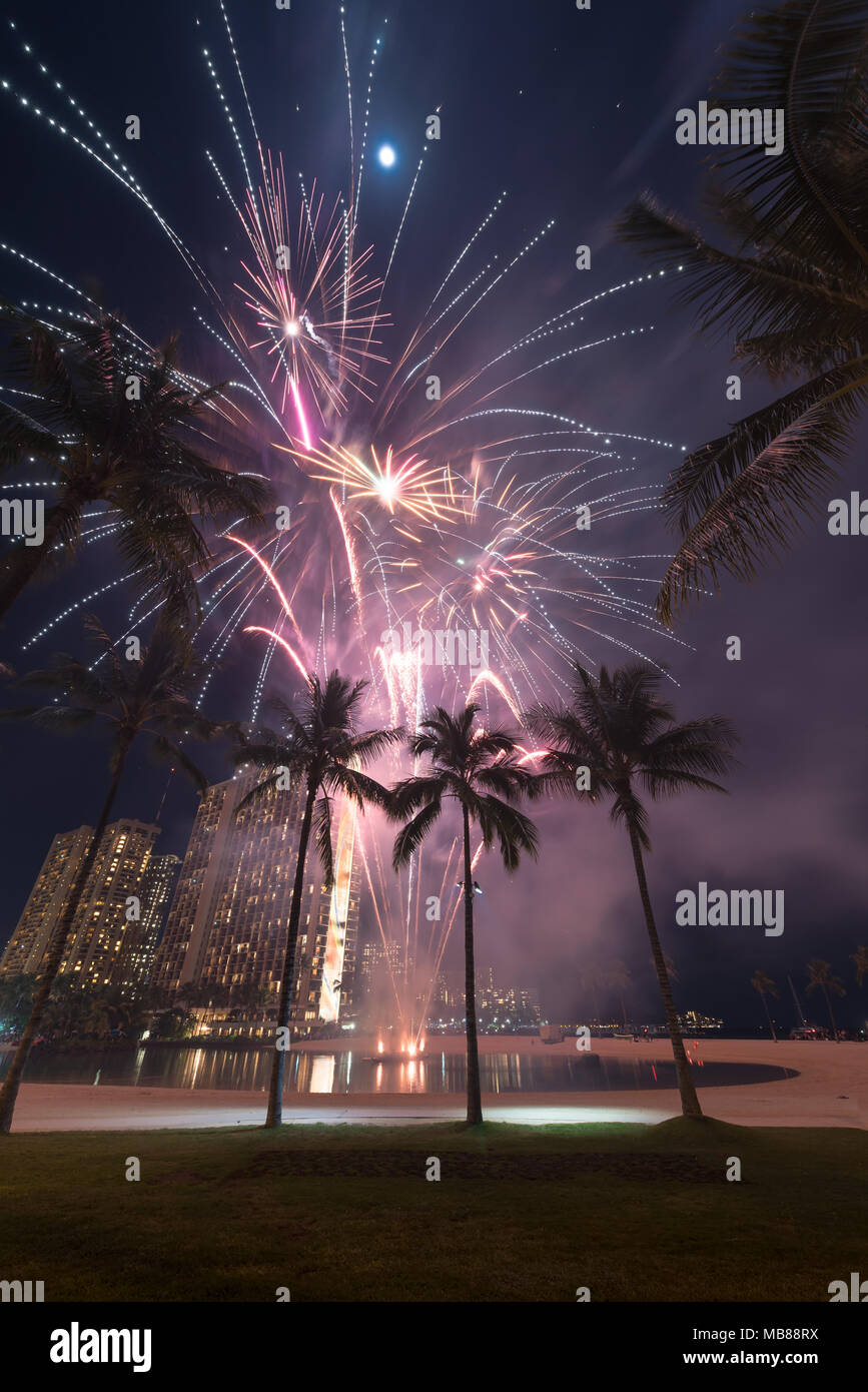 New Year's fireworks at the Hilton Hawaiian Village in Honolulu, Hawaii with the beach, palm trees and a lagoon - Stock Image