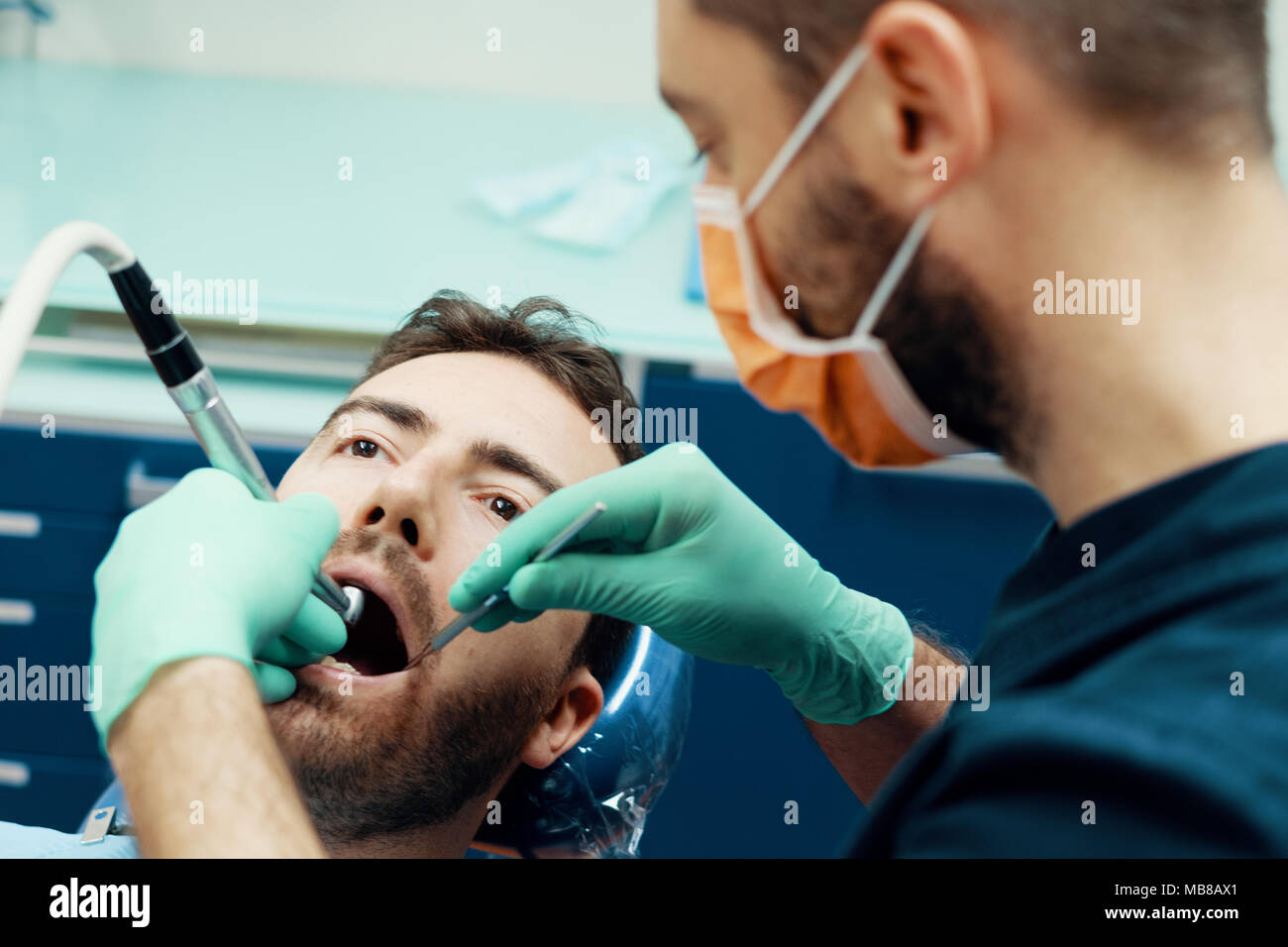 Dentist working in his medical clinic - Stock Image