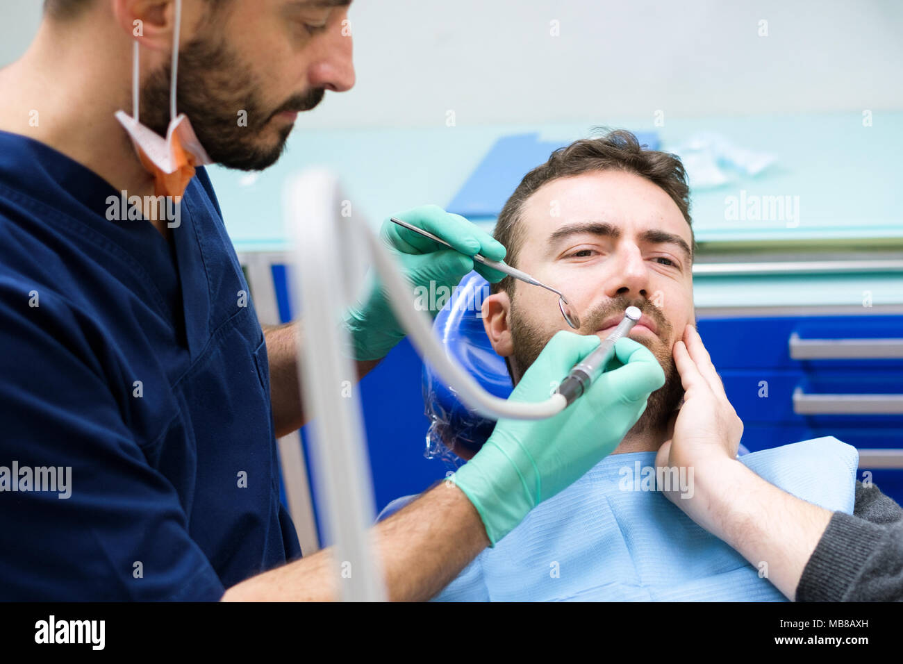 Dentist examining patient teeth in his clinic - Stock Image