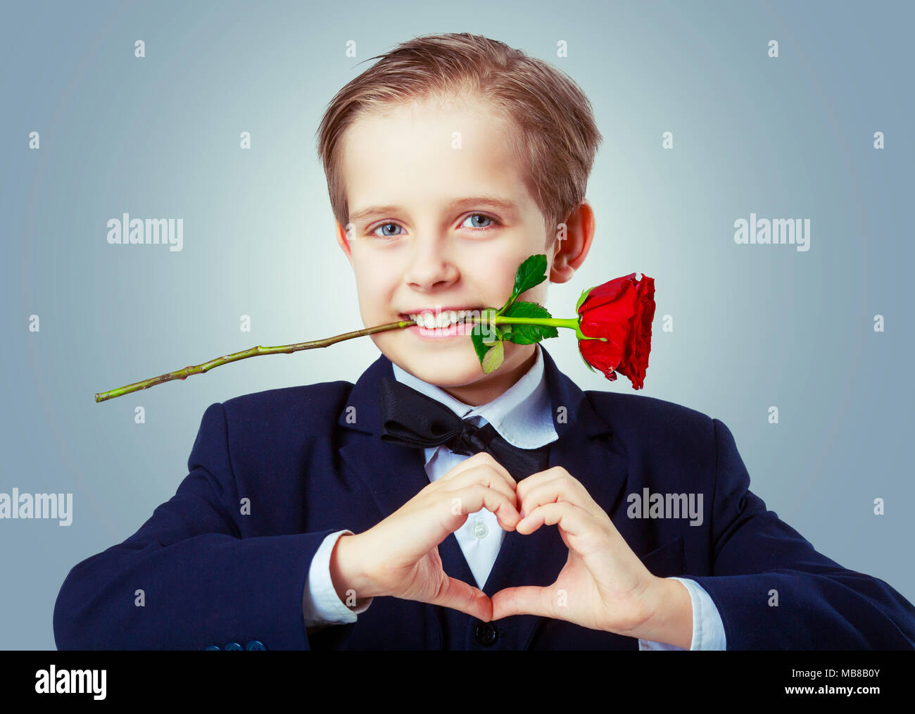 hansome boy wearing a black suit with rose in his teeth, isolated ...