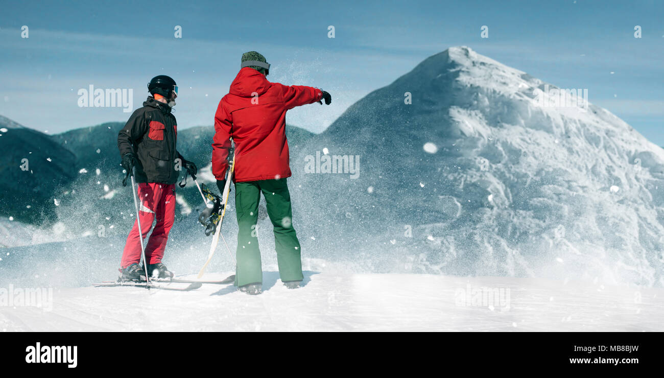 Downhill skiing, two skiers on top of the mountain, blue sky on background. Winter active sport, extreme lifestyle - Stock Image