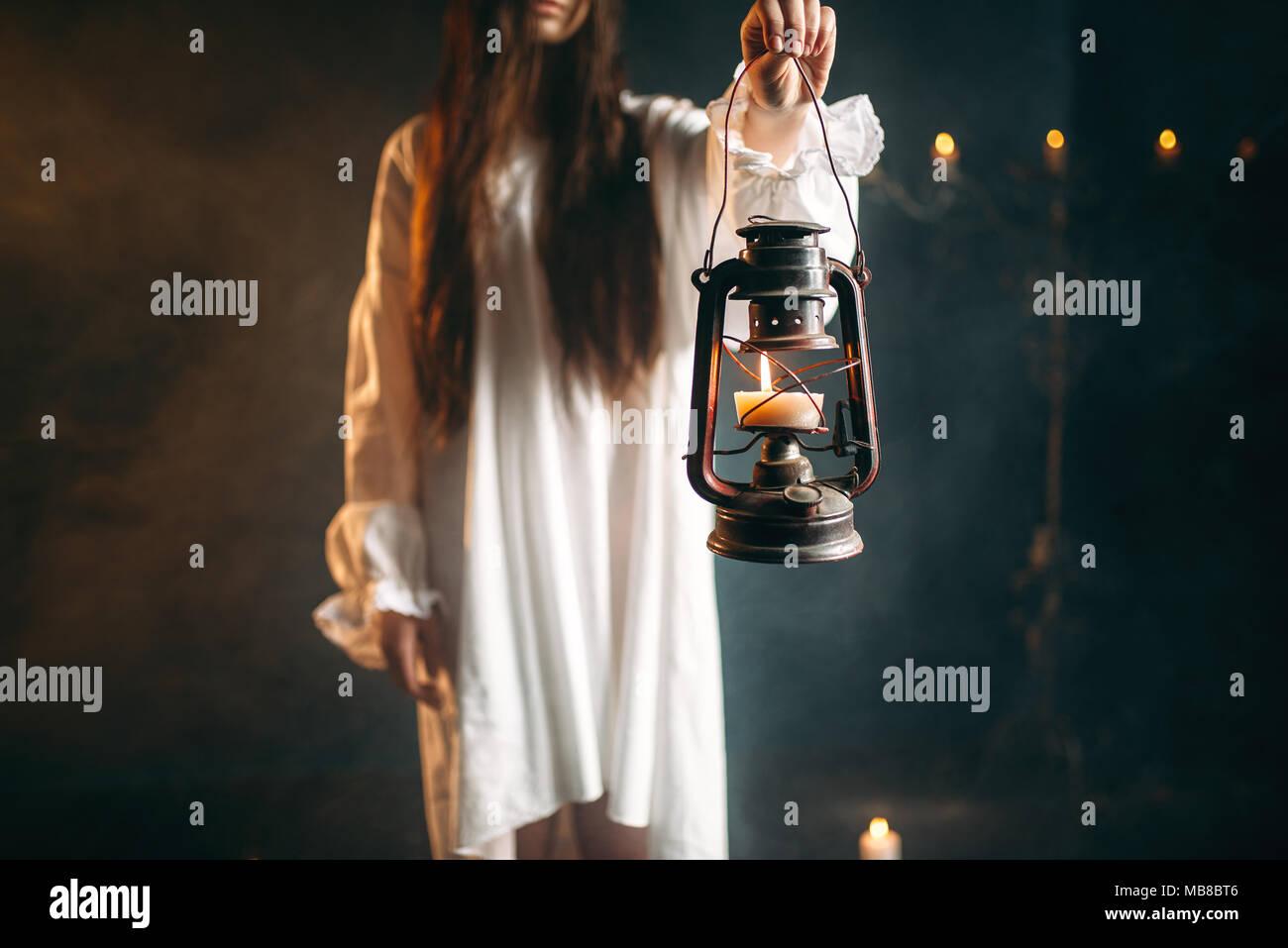 Female person in white shirt holds kerosene lamp in hand. Dark magic ritual, occult and exorcism - Stock Image