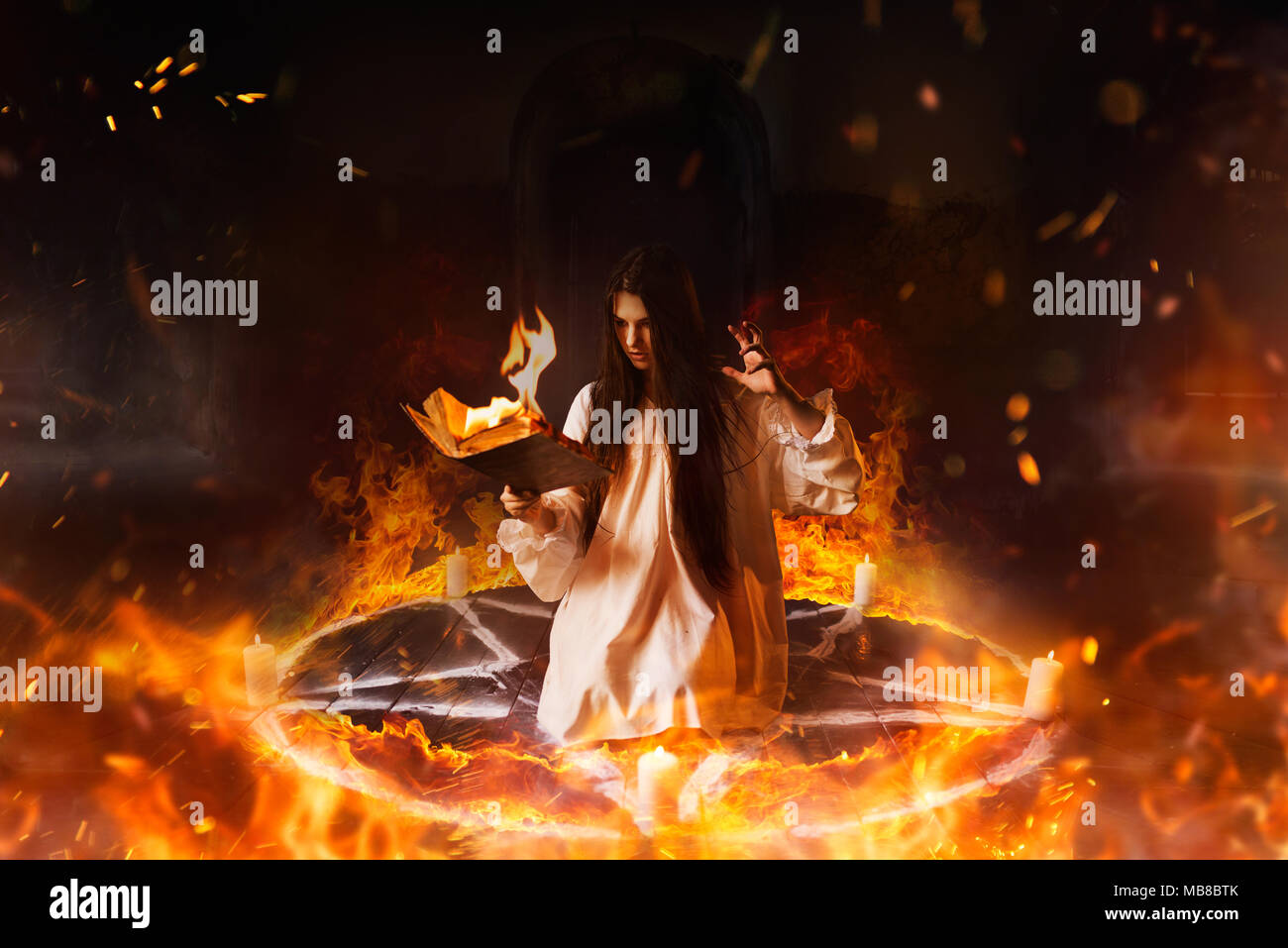 Young woman in white shirt sitting in the center of burning pentagram circle and reads spellbook, gark magic ritual, mysticism - Stock Image