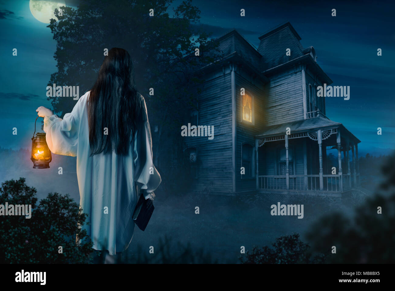 Female person in white shirt holds kerosene lamp and spellbook in hand against abondoned house, moonlit night, back view. Dark magic, occultism and ex - Stock Image