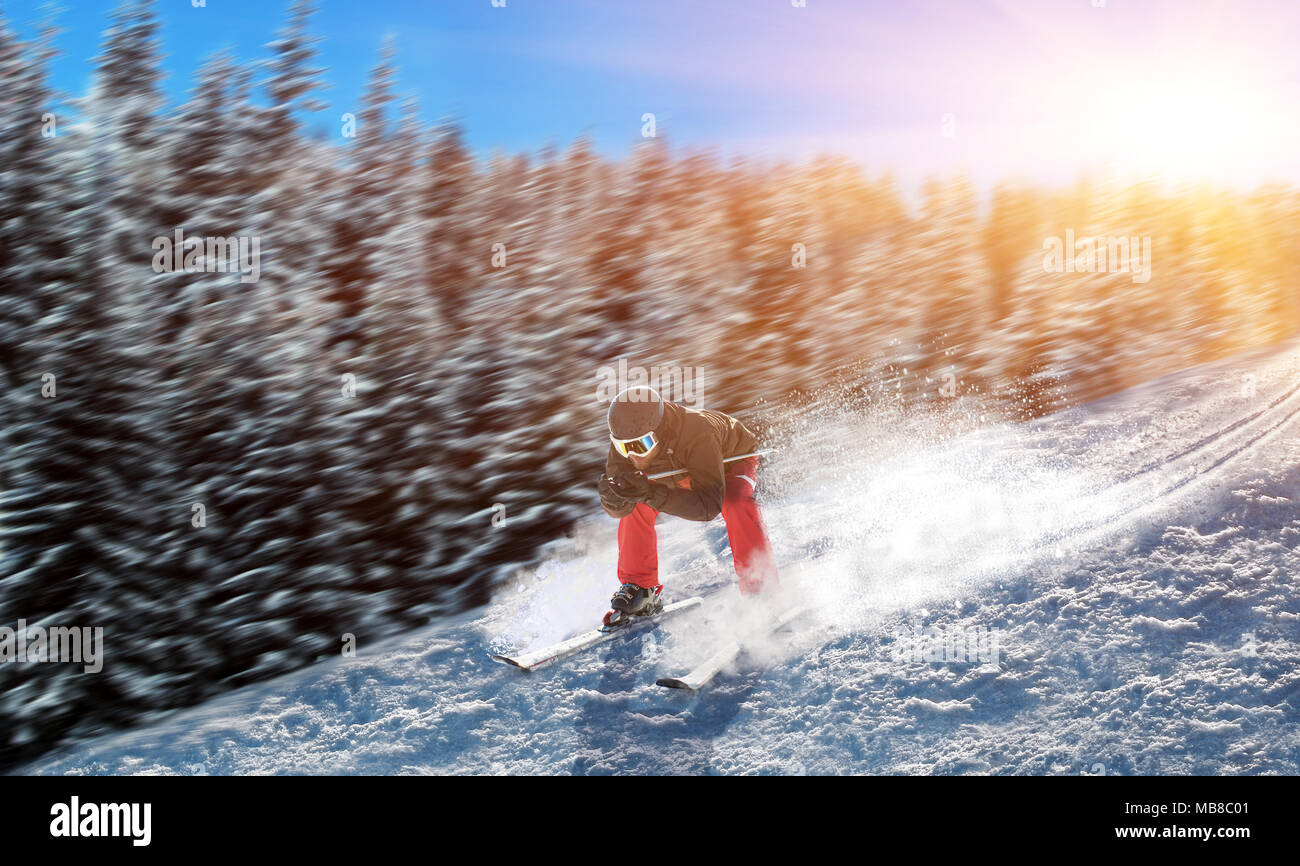 Skier in helmet and glasses racing from the mountain. Winter active sport, extreme lifestyle. Downhill skiing - Stock Image
