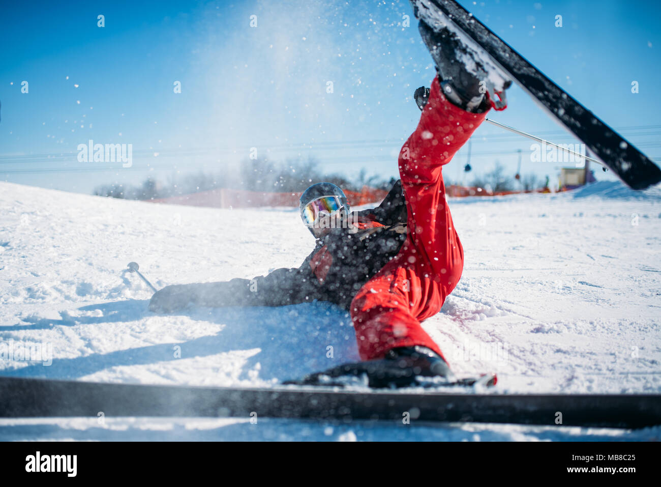 Skier in helmet and glasses lies on snowy mountain. Winter active sport, extreme lifestyle. Downhill skiing - Stock Image