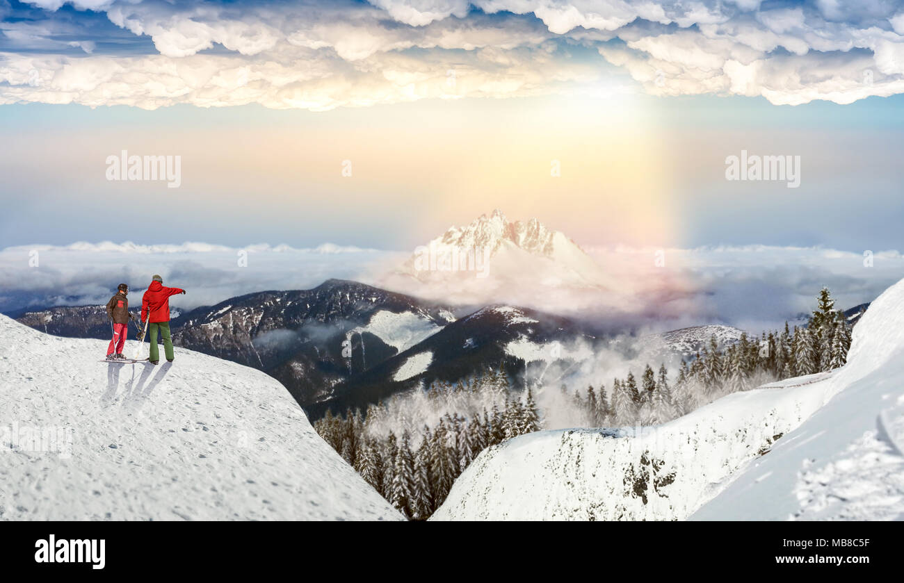 Downhill skiing, male and female skiers on the top of slope, blue sky and rainbow on background. Winter season active sport, extreme lifestyle - Stock Image