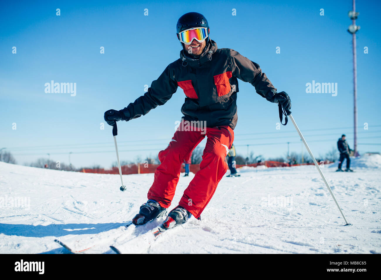 Skier in helmet and glasses riding from speed slope, front view. Winter active sport, extreme lifestyle. Downhill skiing - Stock Image