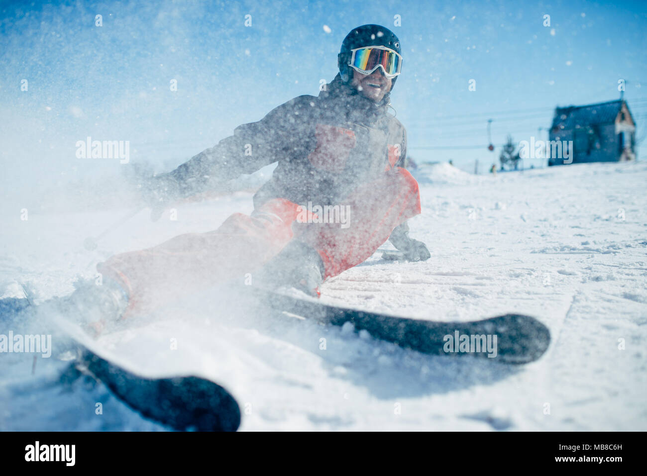 Skier in helmet and glasses lies on snowy surface of speed slope, front view. Winter active sport, extreme lifestyle. Downhill skiing - Stock Image