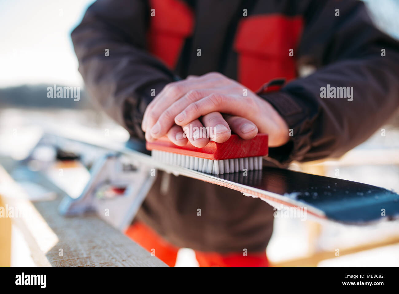 Male skier hands prepares skis for riding. Winter active sport, extreme lifestyle. Downhill skiing - Stock Image