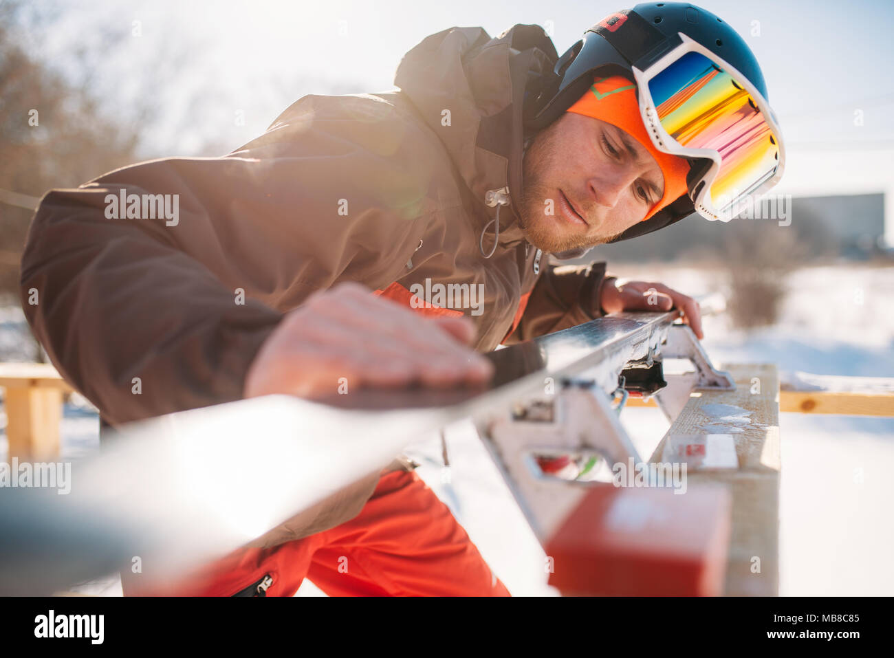 Male skier checks skis before skiing, closeup. Winter active sport, extreme lifestyle. Downhill skiing - Stock Image