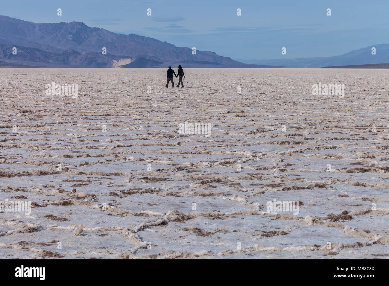 Couple were holding hand and hiking in Badwater Basin in Death Valley National Park, California, United States. - Stock Image