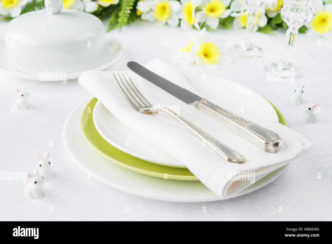 Classic serving for a gala dinner with white and green porcelain plates, silverware and spring flowers on a white tablecloth Stock Photo