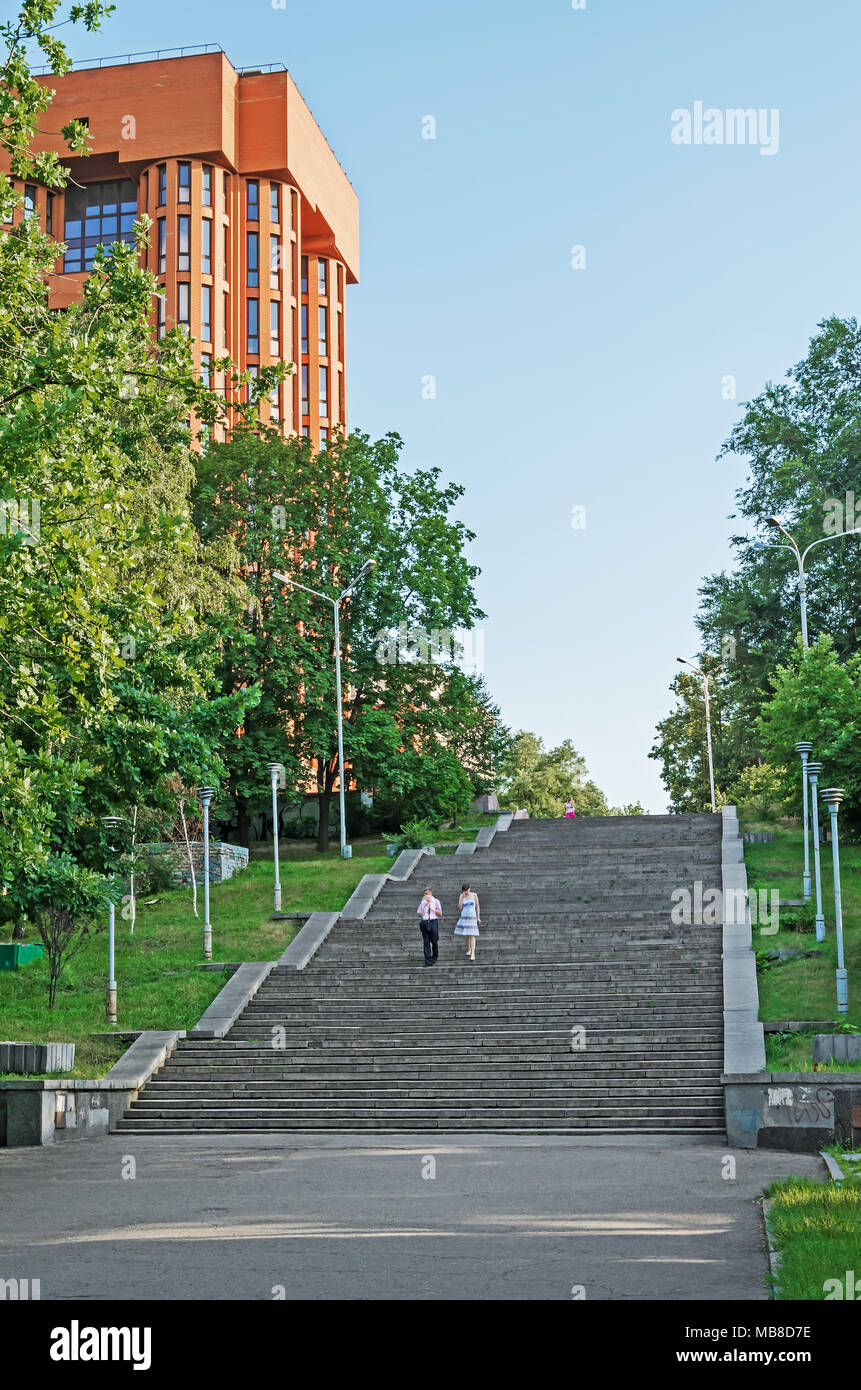 Dnipro, Ukraine - July 05, 2013: In summerly evening pedestrians go on foot the stairs of city park - Stock Image
