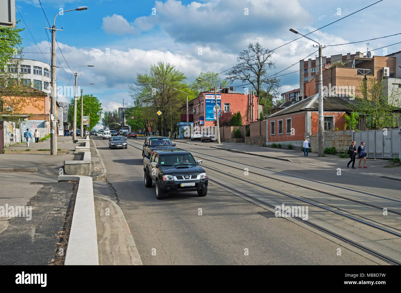 Dnipro, Ukraine - April 19, 2016: Small city street with tram tracks in early spring early in the evening - Stock Image