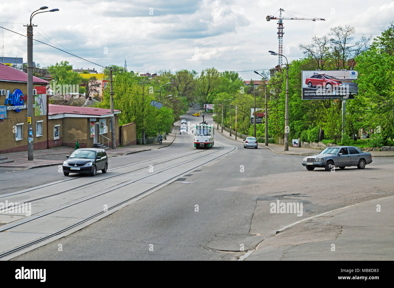 Dnipro, Ukraine - April 19, 2016: Small city crossroad with tram tracks in middle of spring early in the evening - Stock Image