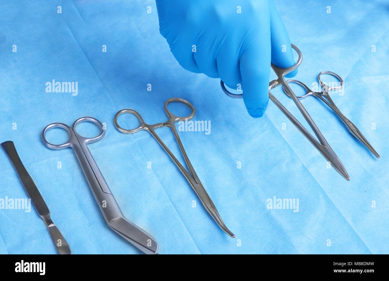 Detail shot of sterilized surgery instruments with a hand grabbing a tool - Stock Image