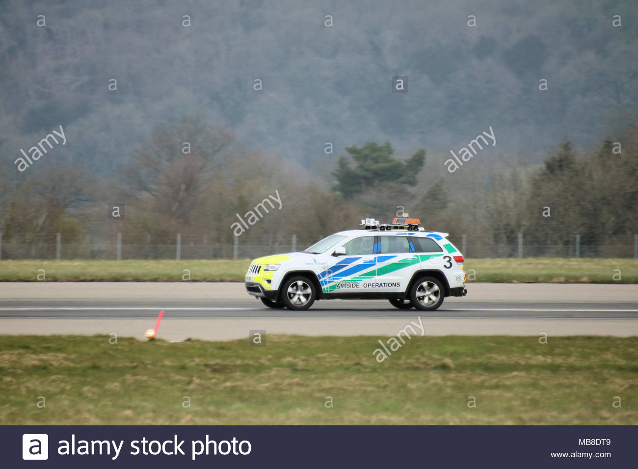 An Airfield Operations vehicle inspects the runway at Bristol Airport just before the next aircraft lands - Stock Image
