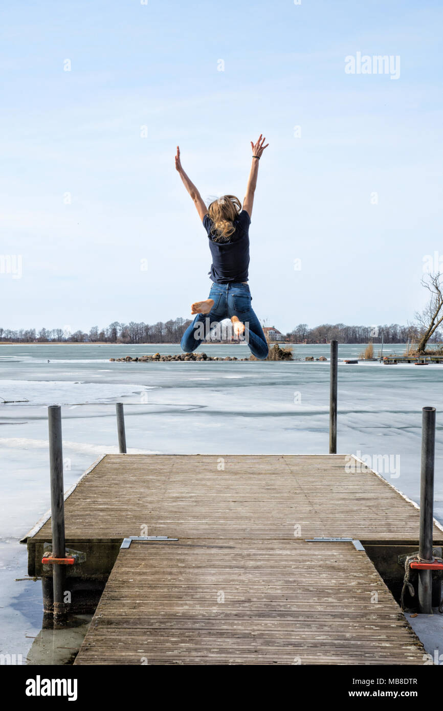 Young girl jumping by the water with spring happiness - Stock Image