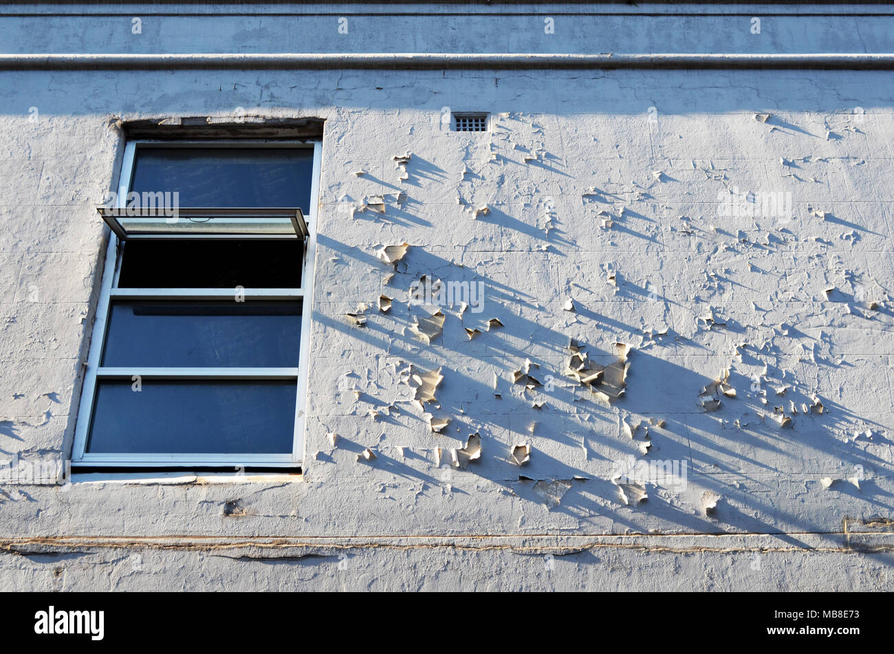 White wall with open window and peeling paint - Stock Image