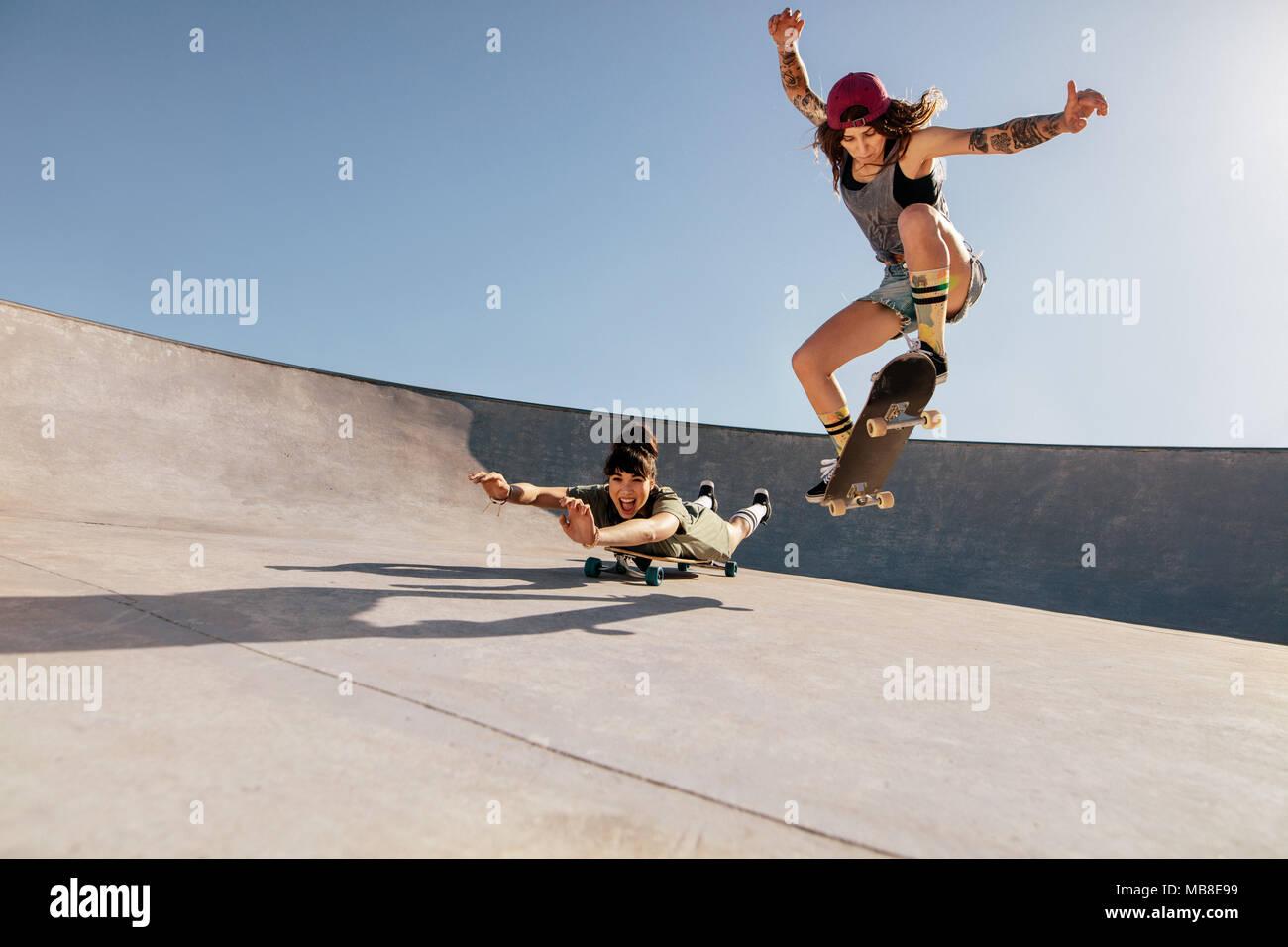 Two women doing stunts on skateboards at skate park. Female friends practising skateboarding outdoors. Stock Photo