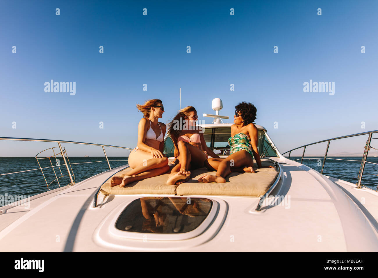 Three girls sitting on the deck of a private yacht in the sea. Smiling female friends in swimsuits relaxing on yacht deck and chatting. - Stock Image