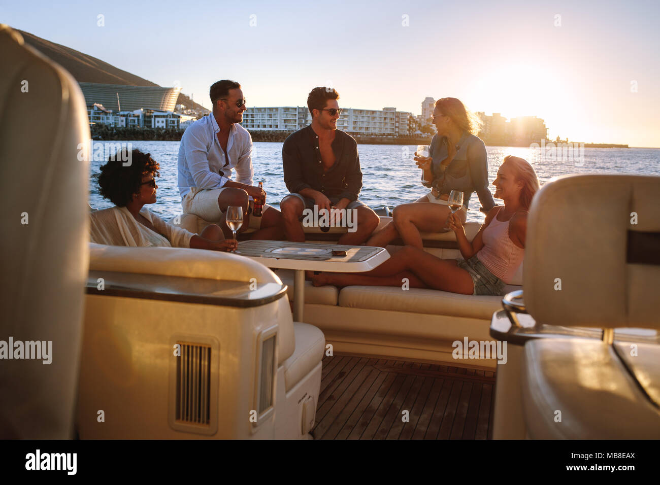 Portrait of young people sitting on a private yacht and drinking. Friends having boat party at sunset. - Stock Image