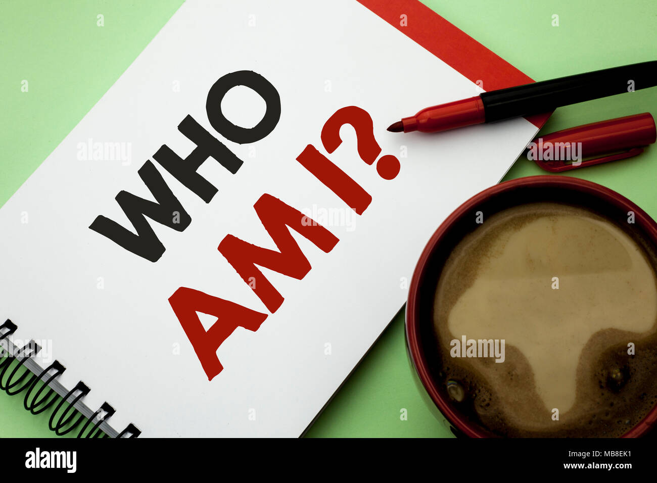 Handwriting text writing Who Am I Question. Concept meaning Question Asked Identity Thinking Doubt Psycology Mystery written on Notebook Book on the plain background Coffee Cup next to it. - Stock Image